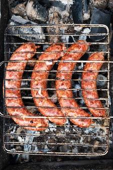 Cozinhar salsichas na grelha na churrasqueira ao ar livre em um piquenique