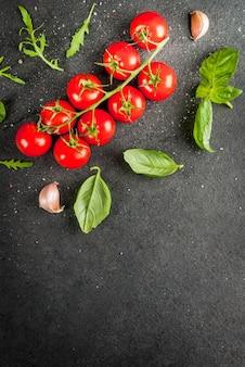 Cozinhar, superfície. ingredientes para cozinhar. especiarias (pimenta salgada) verdes (rúcula salsa manjericão) e coquetel tomate cereja em uma mesa de pedra preta. espaço de cópia da vista superior