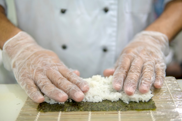 Cozinhar sushi no restaurante. mãos close-up.