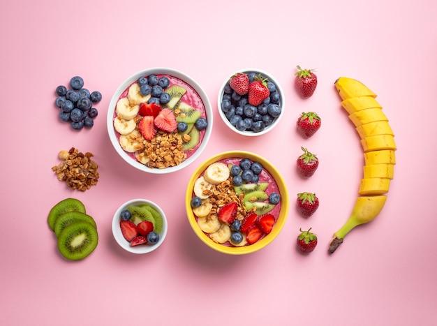 Cozinhar tigela de suco de açaí. ingredientes para fazer uma tigela de smoothie fresco: morangos frescos, banana, mirtilos, kiwis e granola em fundo rosa pastel. close-up, vista de cima, comida saudável