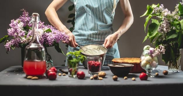 Cozinhar torta caseira de cranberry. uma chef confeiteira preparando um batedor de creme de leite