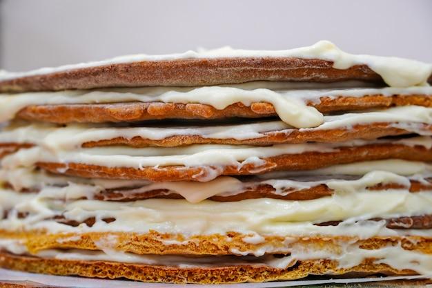 Cozinhar um bolo de aniversário festivo de várias camadas. scones e chantilly. colocar uma camada de bolo de banana para torta suculenta.