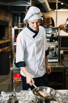 Cozinhe a carne fritando na panela no fogão