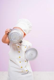 Cozinhe a criança cobrindo o rosto com pote