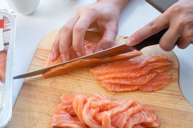 Cozinhe à mão usando uma faca, cortando um salmão fresco em uma tábua de madeira