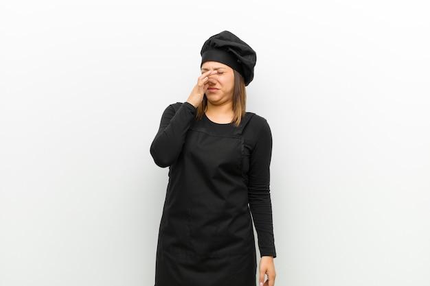 Cozinhe a mulher com nojo, segurando o nariz para evitar cheirar um fedor sujo e desagradável