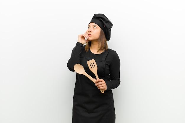 Cozinhe a mulher com um olhar concentrado, imaginando com uma expressão duvidosa, olhando para cima e para o lado