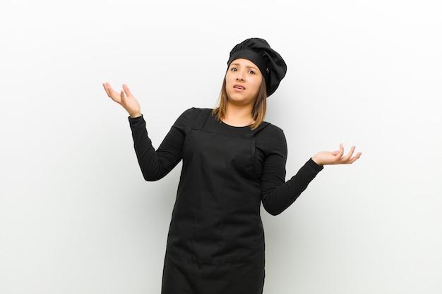 Cozinhe a mulher encolher os ombros com uma expressão idiota, louca, confusa e confusa, sentindo-se irritada e sem noção contra o branco