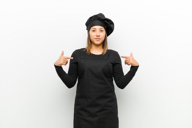 Cozinhe a mulher olhando orgulhosa, positiva e casual, apontando para o peito com as duas mãos contra o branco
