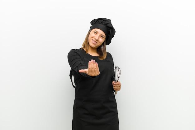 Cozinhe a mulher se sentindo feliz, bem-sucedida e confiante, enfrentando um desafio e dizendo: traga-o! ou recebê-lo contra branco
