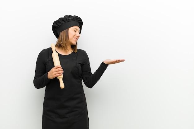 Cozinhe a mulher se sentindo feliz e sorrindo casualmente, olhando para um objeto ou conceito realizado na mão do lado contra a parede branca