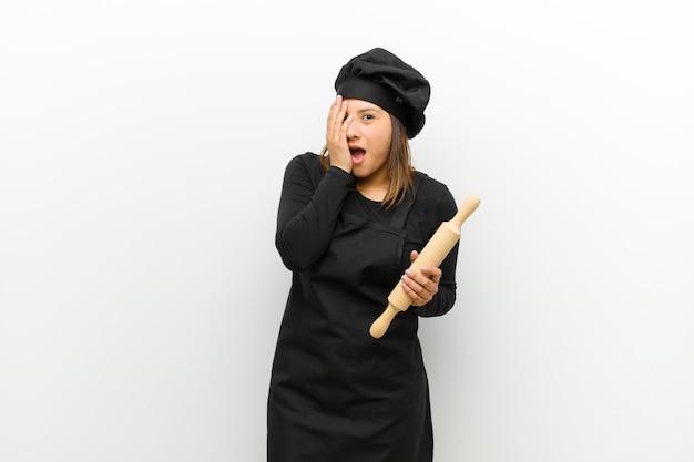 Cozinhe a mulher sentindo medo ou vergonha, espiando ou espiando com os olhos semicobertos com as mãos contra o branco