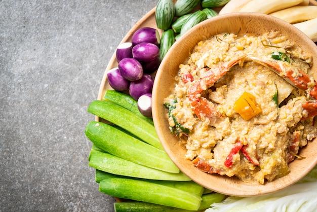 Cozinhe a pasta de pimentão com o caranguejo ou molho de caranguejo e soja com leite de coco e legumes