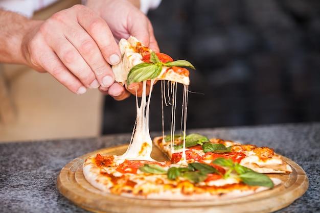 Cozinhe a preparar a pizza em um restaurante.