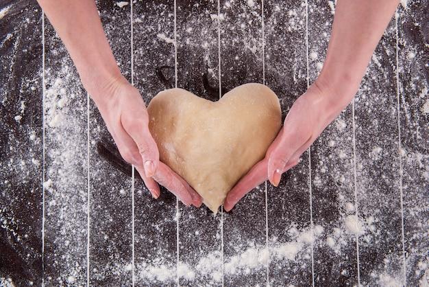 Cozinhe a preparar massa para assar na cozinha