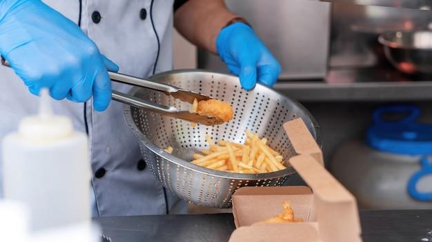 Cozinhe adicionando carne frita e batatas fritas aos pratos em um food truck