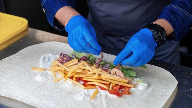 Cozinhe adicionando cebola em um embrulho em um food truck
