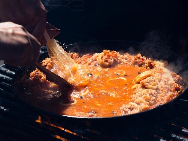 Cozinhe adicionando molho ao arroz com anéis de lula e legumes na frigideira