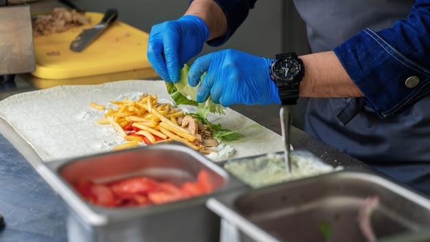 Cozinhe adicionando salada em um embrulho em um food truck