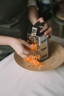 Cozinhe as cenouras esfregadas em um ralador em uma tigela. mulher rala cenouras em um ralador. fora de foco, turva