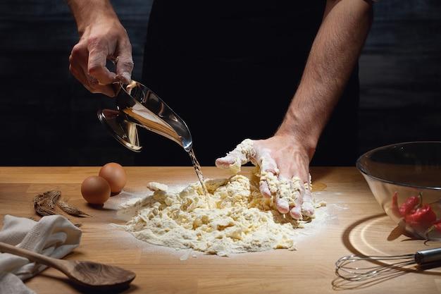 Cozinhe as mãos amassando a massa, adicionando água à farinha