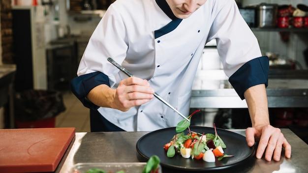 Cozinhe colocando espinafre no prato grande com salada