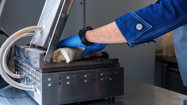 Cozinhe colocando uma embalagem para assar em um food truck