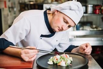 Cozinhe colocando vegetais no prato com salada