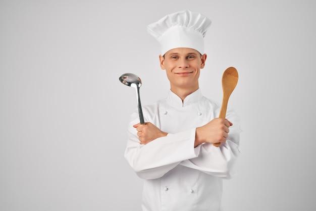 Cozinhe com uma concha e uma colher de pau em trabalhos de cozinha de mãos