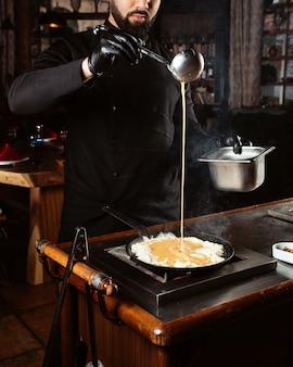 Cozinhe derrama ovos enchendo a panela