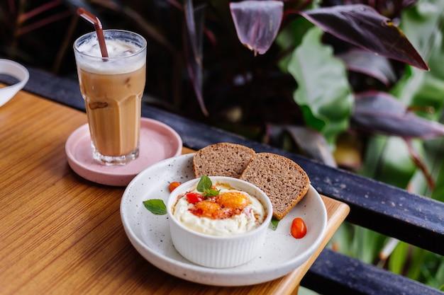 Cozinhe dois ovos com presunto e queijo em uma tigela redonda com dois pedaços de pão integral saudável ao lado