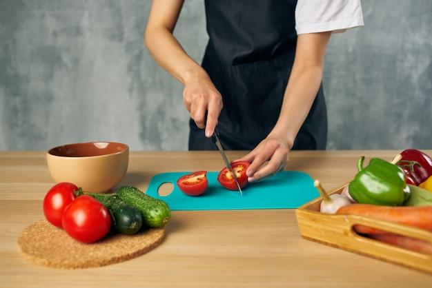 Cozinhe em avental preto cozinhando alimentação saudável dieta de salada