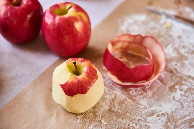 Cozinhe em casa. maçã descascada madura. cozer os ingredientes colocados na mesa, pronta para cozinhar. conceito de preparação de alimentos, mesa branca em fundo