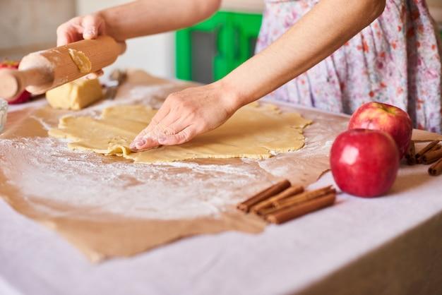Cozinhe em casa. mulher amassar massa para a torta de maçã na mesa da cozinha. estilo rústico