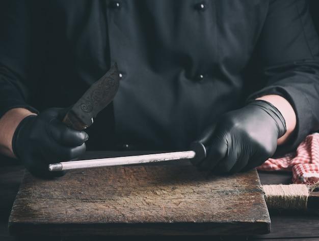 Cozinhe em luvas de látex preto afia uma faca sobre uma mesa de madeira