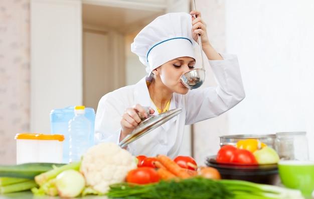 Cozinhe em uniforme branco teste sopa de concha