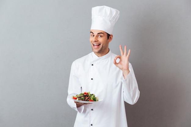 Cozinhe em uniforme segurando salada mostrando o gesto bem.