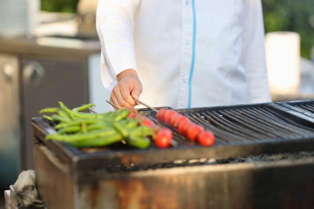 Cozinhe em vegetais grelhados de casaco branco na cozinha de verão.