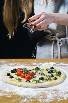 Cozinhe esfrega queijo em um foccacia caseiro.