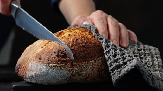 Cozinhe fatiando pão fresco em uma tábua de madeira preta