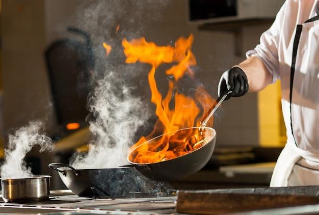 Cozinhe fazendo o jantar na cozinha do restaurante high-end.