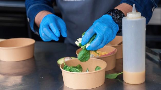Cozinhe fazendo salada, adicionando ingredientes, caminhão de comida