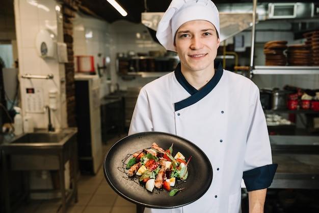 Cozinhe mostrando salada com carne na chapa