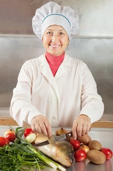 Cozinhe mulher cozinhando peixe