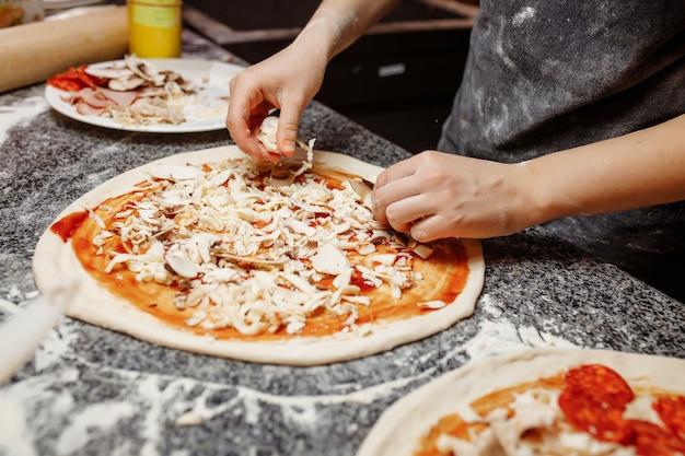 Cozinhe na cozinha colocando os ingredientes na pizza. conceito de pizza. produção e entrega de alimentos.