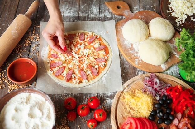 Cozinhe na cozinha colocando os ingredientes na pizza.