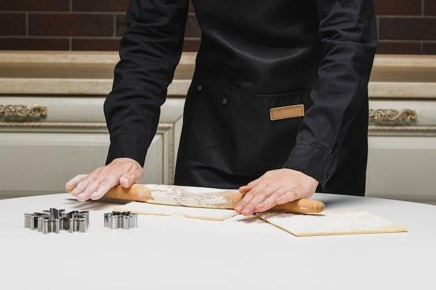 Cozinhe o chef rola a massa para os biscoitos.