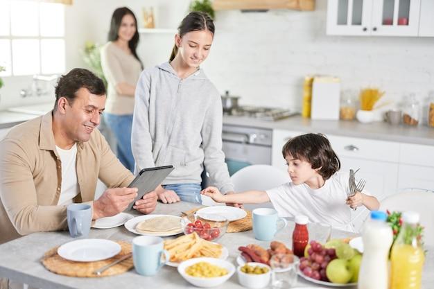 Cozinhe para servir ao amor. marido latino de meia-idade usando o tablet pc, assistindo ao noticiário, esperando pelo jantar, enquanto seus filhos e esposa serviam a mesa na cozinha em casa