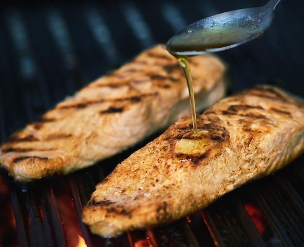 Cozinhe preparando o salmão na grelha com manteiga e ervas finas