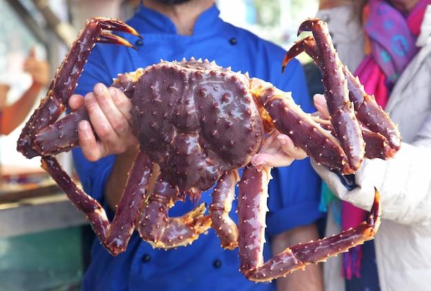 Cozinhe segurando um caranguejo grande